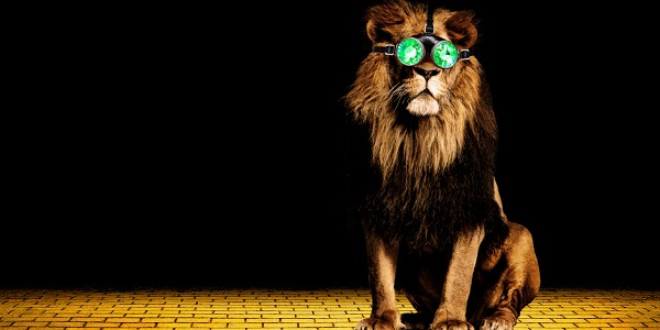 A large lion with emerald green steam punk glasses sits on the centre right of a yellow brick road which fades into blackness