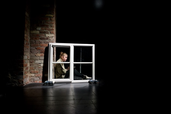 Photo of darkened stage. In the centre is the white crossed frame of a window. Behind, a woman sits on the floor looking out as she leans against a brick wall