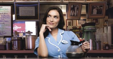 Photograph of Chelsea Halfpenny. She is dressed as an American diner waitress in light blue dress. She holds a pot of coffee whilst leaning her head on her hand and looking off into the distance. In the background is a typical cafe/diner. Cups, coffee machines, signs